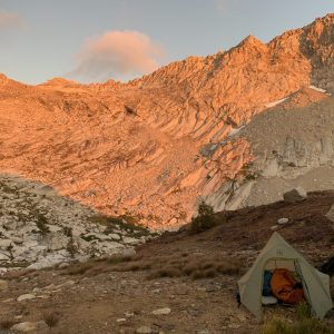 A tent sits on rocky earth as a golden glow spreads across the mountain tops.