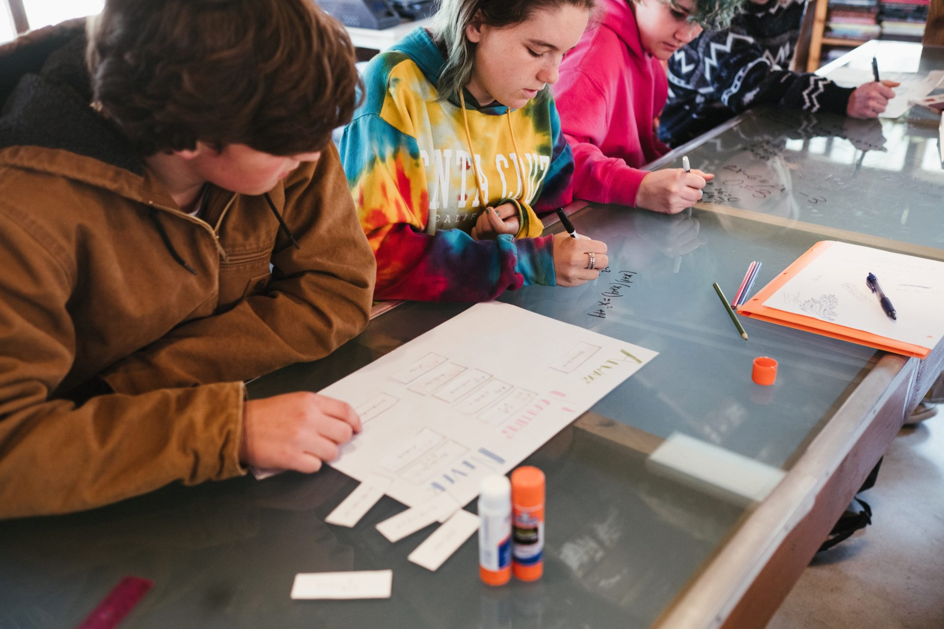 Four students sit next to each other at a clear dry-erase board–topped table. The three students furthest from the camera each scribble with black dry erase markers while the student closest to the camera manipulates slips of paper on a larger piece of paper, glue sticks at the ready for pasting the slips down when answers are acertained.
